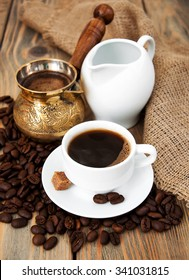 coffee cup with coffee beans,    milk jug and turk on a wooden background