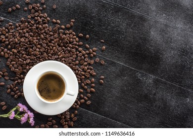 coffee cup with beans on the black  wooden  background. And the space for your text.