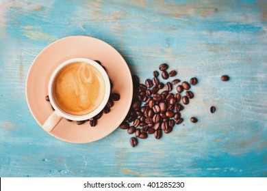 Coffee cup and coffee beans on blue background. Top view.
