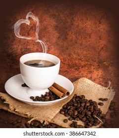 Coffee cup and coffee beans on brown background