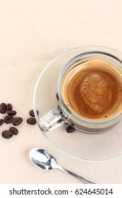 Coffee cup and coffee beans on canvas background