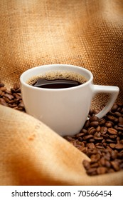 Coffee cup and beans on jute background