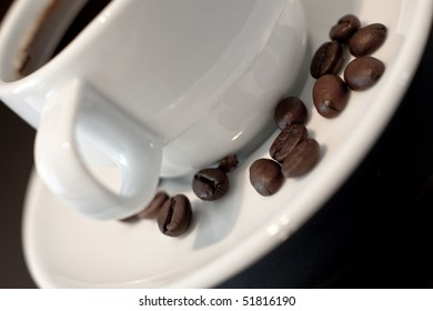 A coffee cup with coffee beans on the plate.