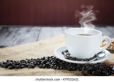 Coffee cup and beans on a rustic background. Coffee Espresso and a curl. Cup Of Coffee and coffee beans on table