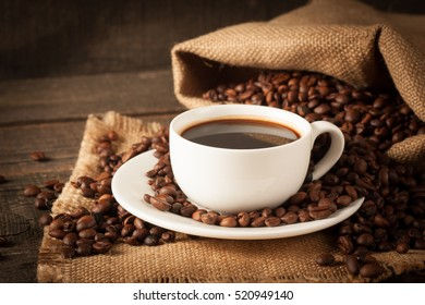 Coffee cup and beans on a rustic background. Coffee Espresso and a piece of cake with a curl. Cup Of Coffee and coffee beans on table