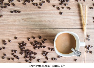 Coffee cup and coffee beans on table with morning sun.