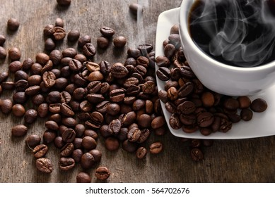 Coffee cup and beans on texture wooden table. Rustic morning still life.