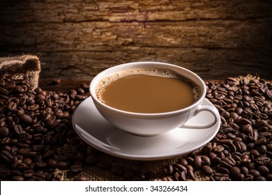 Coffee cup and coffee beans on vintage wooden background