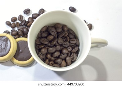 Coffee cup and coffee beans on white background. Top view.