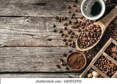 Coffee cup with coffee beans on wood background.