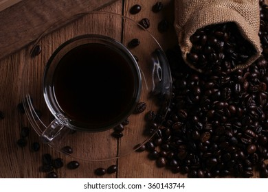 Coffee cup and coffee beans on wood background.(Vintage effect style pictures)