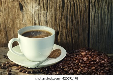 Coffee cup and coffee beans on a wood background