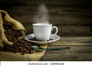 Coffee cup with coffee beans on wooden .