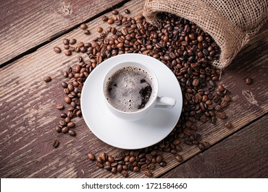 Coffee cup and beans on a wooden table.