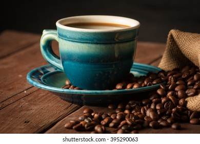 Coffee cup with coffee beans on wooden sacking background with anise and cinnamon