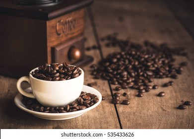 coffee cup and coffee beans on wooden table