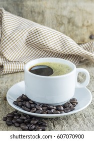 Coffee cup and coffee beans on wooden table.