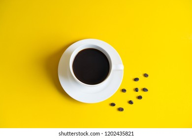 Coffee cup and coffee beans on yellow background