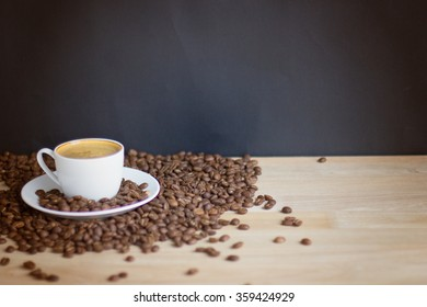Coffee cup and beans over wood