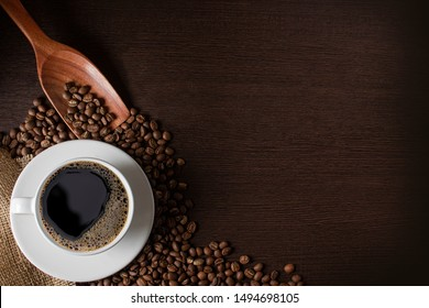 coffee cup and beans placed on a wooden board With copy space for text.