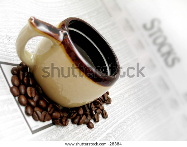 coffee cup and beans sitting on the stocks section of the newspaper.