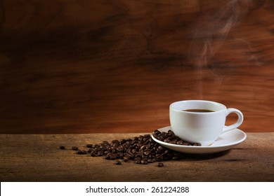 Coffee cup and coffee beans with stream on old wooden background