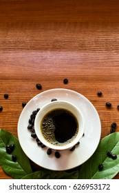 Coffee cup and coffee beans top view on wooden table background