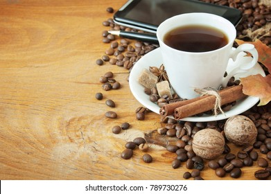 Coffee cup with coffee beens, spices, nuts and mobile phone on wooden background. Coffee break concept