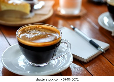 Coffee cup with blurred behind pen on  notebook.