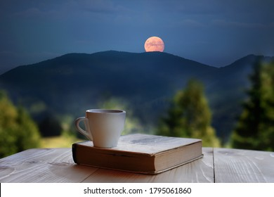 A coffee cup and a book against the backdrop of a mountain landscape with a full moon coming out from behind the mountains. Cozy atmosphere of the evening in a secluded place in nature.