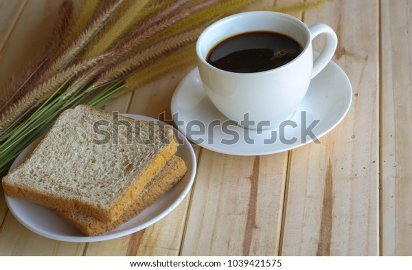 Coffee cup and bread on the table in the morning