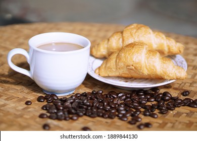 Coffee in a cup with butter croissant
