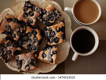 Coffee in the cup and cake with blueberries on the plate. The two-kolor mat is a background. - Shutterstock ID 1474514525
