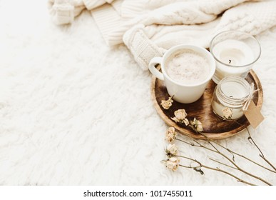Coffee cup with candles in cozy home atmosphere. Warm sweater and dry flowers