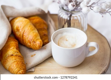 Coffee cup cappuccino with cream and tasty baked croissants. Morning breafast with croissants buns and fresh coffee