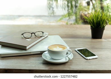 Coffee cup and cell phone and laptop computer with glasses on wooden table.