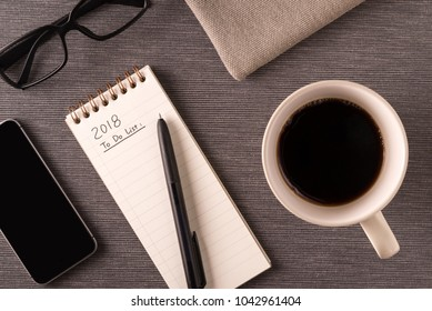 Coffee cup, cellphone, glasses and new year plan being written
