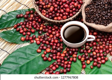 coffee cup and cherry coffee coffee beans on wood table, americano cups