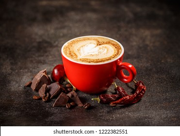Coffee cup with chili peppers and chocolate on a dark vintage background