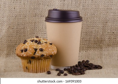 Coffee cup and chocolate chips muffin on jute background.
