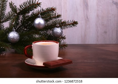 Coffee cup and chocolate on wooden table texture. Coffeebreak. Christmas time