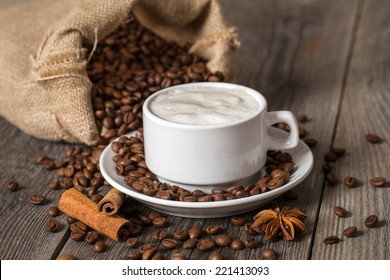 Coffee cup with cinnamon sticks and coffee bag on wooden table.