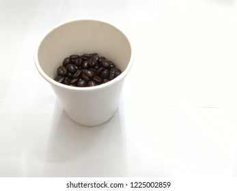 Coffee cup and coffeebeans on a white background.