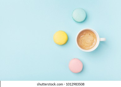 Coffee cup and colorful macaron on pastel blue background top view. Cozy morning breakfast. Fashion flat lay style. Sweet macaroons.