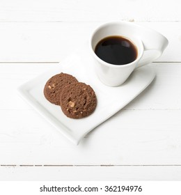 coffee cup with cookie on white wood background