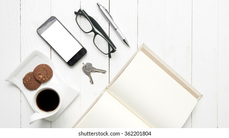 coffee cup with cookie,phone,open notebook and eyeglasses on white wood table