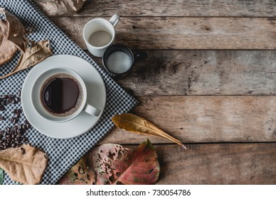 Coffee cup, creamer and sugar on wooden table background with copy space, coffee time concept. Top view