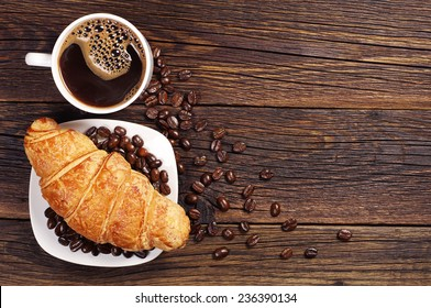 Coffee cup with croissant for breakfast on a dark wooden table, top view - Shutterstock ID 236390134