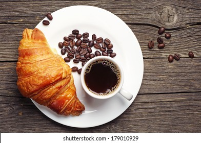 Coffee cup with a croissant on vintage wooden table. Top view