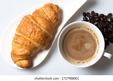 Coffee cup and croissant on white background , top view